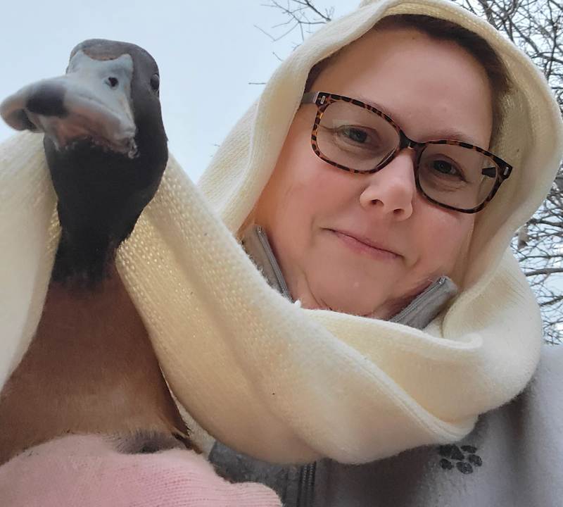 woman in a gray fleece coat and tortiseshell glasses with a white scarf over her head and draped over the head of the brown duck she's holding.